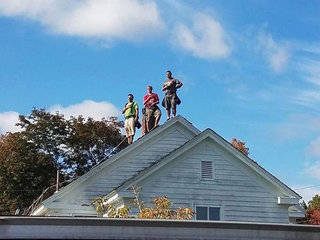 3 roofers set hammers aside to stand for anthem